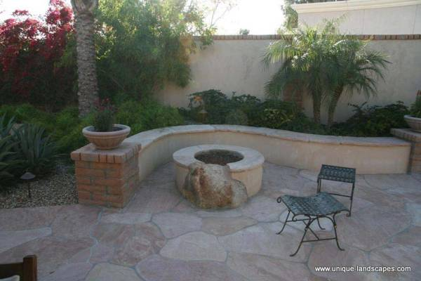 This creative little nook has blended many different materials like flagstone, brick, mortar, and even a boulder into the firepit wall itself