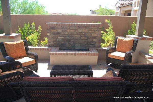 A more formal firepit that adds interest to a large privacy wall with it's shape and materials.