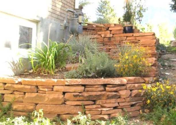 A steep corner is altered with a nicely stacked natural stone wall.