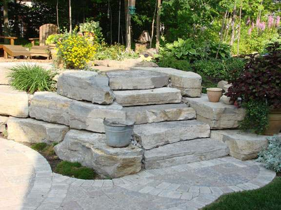 A slope tamed with natural stone steps and a wall.