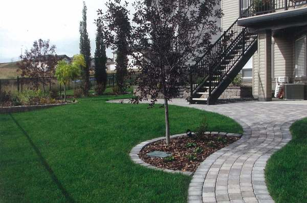 A simple brick pathway flows right out of the patio to another place in the yard.
