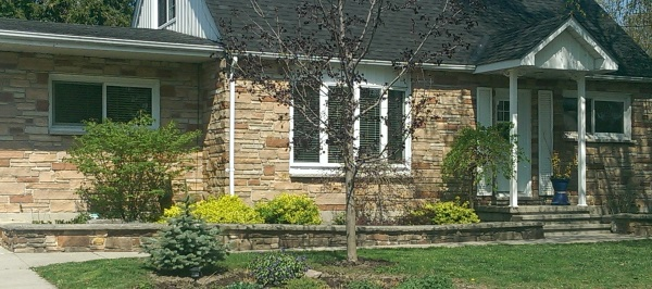 A low mortared fieldstone wall compliments the stone wall facing on this home. The wall is topped off with manufactured capping stone.