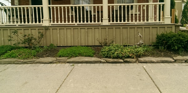 Even a small front yard can still have a little curb appeal along the sidewalk. A simple one tiered stone wall dresses up a front porch on this older home.