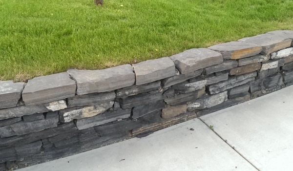 Dry stacked stone wall in Calgary made from Rundlestone. Rundlestone is a popular choice in the region that is quarried from the nearby Banff area.